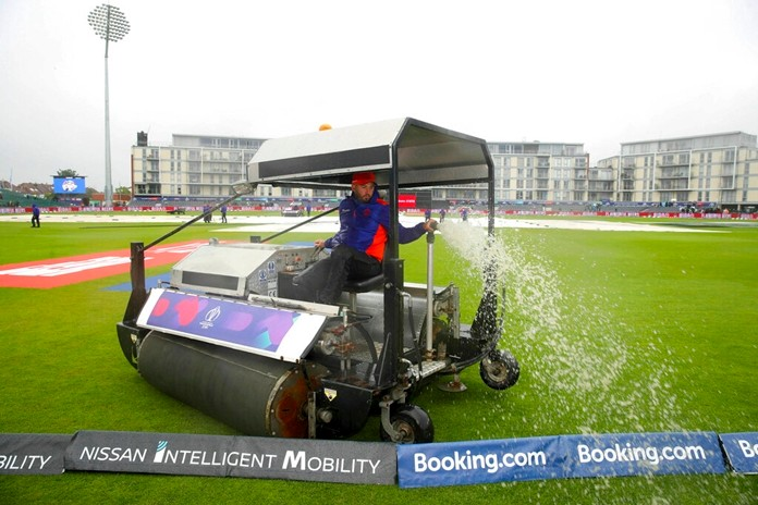 Ground staff clear water from the pitch at the ICC Cricket World Cup group stage match at the County Ground in Bristol. England, Tuesday June 11, 2019. (Nick Potts/PA via AP)