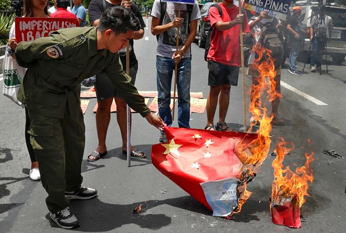 A protester burn a Chinese national flag during a rally outside the Chinese Consulate in Manila, Philippines, Wednesday, June 12, 2019. (AP Photo/Aaron Favila)