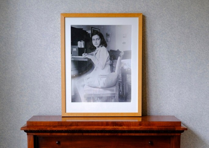 A photo of Anne Frank stands on a replica of the writing desk she once used in her family's former apartment in Amsterdam, Netherlands, Wednesday, June 12, 2019. (AP Photo/Michael C. Corder)