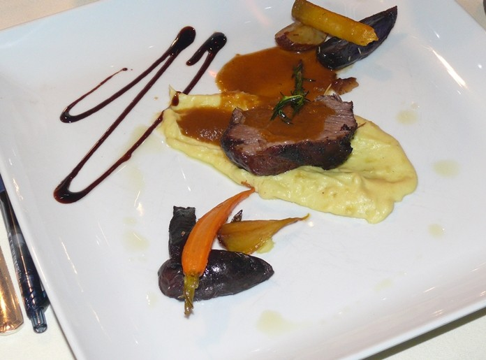 A slow cooked marinated rump of lamb on a light wasabi mash with herb reduction and roasted roots.