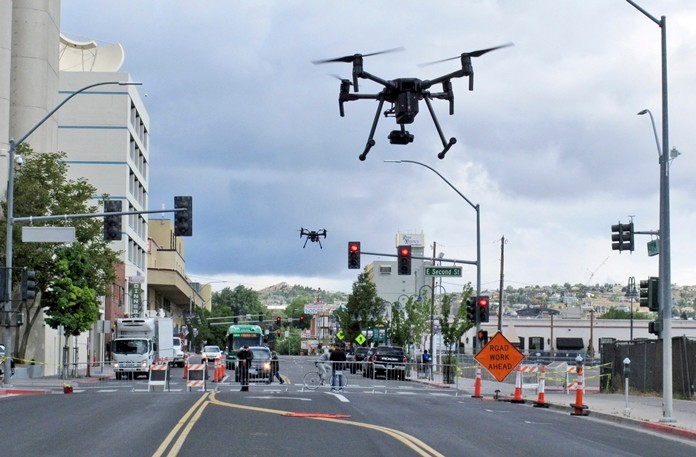 In this May 21, 2019 photo, two drones fly above Lake Street in downtown Reno, Nev. as part of a NASA simulation to test emerging technology that someday will be used to manage travel of hundreds of thousands of commercial, unmanned aerial vehicles (UAVs) delivering packages. It marked the first time such tests have been conducted in an urban setting. (AP Photo/Scott Sonner)
