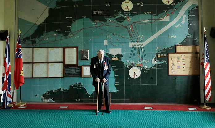 British D-Day veteran Leonard 'Ted' Emmings poses for photographs backdropped by the map used to plan the Normandy D-Day landings during a D-Day 75th anniversary media facility at Southwick House near Portsmouth, England. Emmings has had a mission for 75 years. The night before the D-Day landings, Emmings and his shipmates on a Royal Navy landing craft learned their mission was to ferry 36 Canadian troops to Juno Beach, a stretch of Normandy coast fortified with artillery, mortars, mines and machine gun emplacements. The men made a pact: Whatever happened, they would look after those who didn't make it back. (AP Photo/Matt Dunham, File)