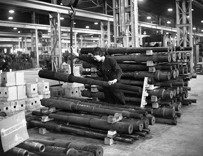 In this May 9, 1941 file photo, a woman stacks anti-tank gun barrels, with the aid of an overhead crane, at a Ministry of Supply factory in Wales, England. Legions of women built weapons of war that men fought and killed with. (AP Photo, File)