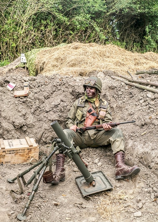 Sevak Hancerli, 23, from Paris, sits in a trench in the WWII reenactors camp of Old Abe next to Saint-Come-du-Mont, Normandy, France, Monday June 3, 2019. Dressed as an American soldier, he was attending the D-Day commemorations for the first time. (AP Photo/Rafael Yaghobzadeh)