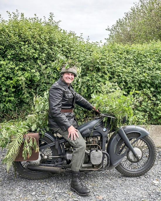 OIliver Ofrijo, 48, from Germany, poses with an old BMW vehicle, in the WWII reenactors camp of Old Abe next to Saint-Come-du-Mont, France, on Monday June 3, 2019. (AP Photo/Rafael Yaghobzadeh)