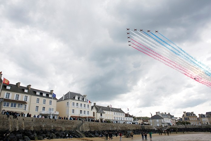 Spectators watch as jets perform a flyover during events to mark the 75th anniversary of D-Day in Arromanches, Normandy, France, Thursday, June 6, 2019. Standing on the windswept beaches and bluffs of Normandy, a dwindling number of aging veterans of history's greatest air and sea invasion received the thanks and praise of a world transformed by their sacrifice. The mission now, they said, was to honor the dead and keep their memory alive, 75 years after the D-Day operation that portended the end of World War II. AP Photo/Thibault Camus)