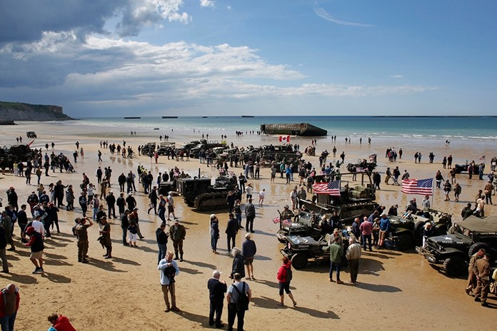 People walk among vintage World War II vehicles parked on the beach during events to mark the 75th anniversary of D-Day in Arromanches, Normandy, France, Thursday, June 6, 2019. (AP Photo/Thibault Camus)