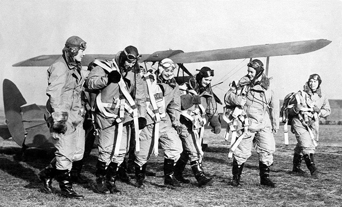 In this Jan. 10, 1940 file photo, some of the nine women who were tasked to take a squadron of Royal Air Force trainer planes from the manufacturing plant, the first time women were allowed to enter a British Military Aircraft, go out on a flying field in England. (AP Photo, File)