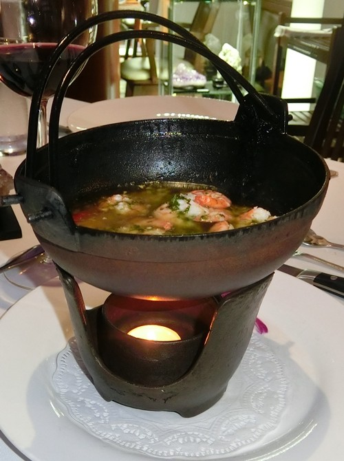 Garlic prawns in an iron pot.