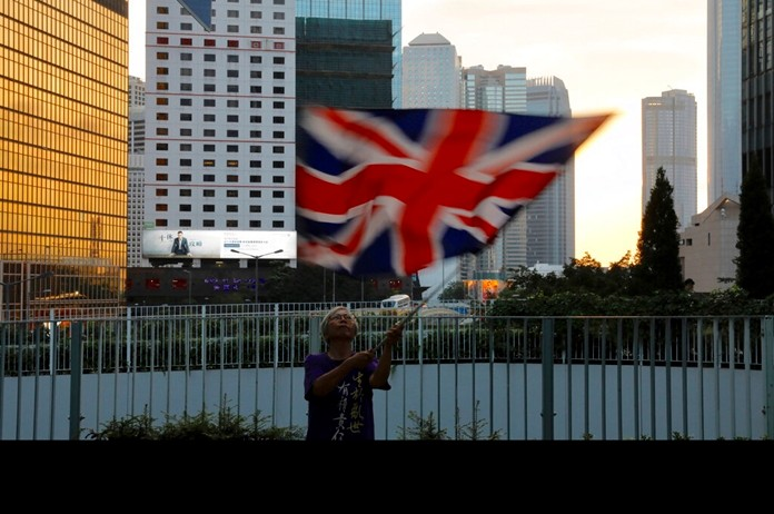 A protester waves a British flag outside the government headquarters in Hong Kong on Saturday, June 15, 2019. (AP Photo/Vincent Yu)