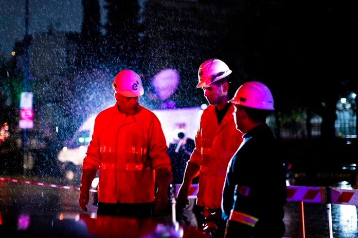 Technicians of Edenor Electricity Company stand under the rain as they work to fix a generator during a blackout in Buenos Aires, Argentina, Sunday, June 16, 2019. (AP Photo/Tomas F. Cuesta)