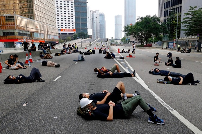 Protesters who camped out overnight take a rest along a main road near the Legislative Council after continuing protest against the unpopular extradition bill in Hong Kong, Monday, June 17, 2019. (AP Photo/Vincent Yu)
