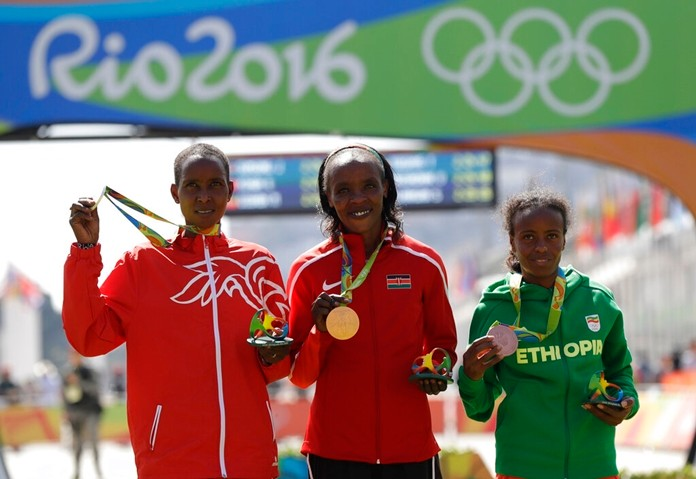 In this Sunday, Aug. 14, 2016 file photo, silver medalist Eunice Jepkirui Kirwa, of Bahrain, left, gold medalist Jemima Jelagat Sumgong, of Kenya, center, and bronze medalist Mare Dibaba, of Ethiopia stand on the podioum after the women's marathon at the 2016 Summer Olympics in Rio de Janeiro, Brazil. (AP Photo/Robert F. Bukaty)