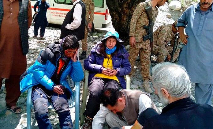 Mountaineers receive initial treatment following their rescue, at a helipad in the town of Imit, Ghizer district of Gilgit Balistan region, Pakistan, Tuesday, Jun 18, 2019. (Gilgit Baltistan regional police department via AP)
