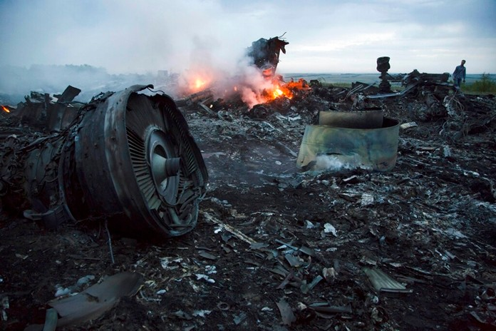 In this Thursday, July 17, 2014 file photo, a man walks amongst the debris at the crash site of Malaysia Airlines Flight 17 near the village of Hrabove, Ukraine. (AP Photo/Dmitry Lovetsky)