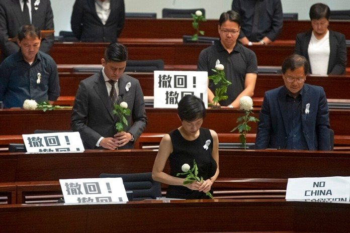 Pro-democracy lawmakers pay a silent tribute to the man who fell to his death on Saturday evening after hanging a protest banner on scaffolding on a shopping mall, at the Legislative Council in Hong Kong, Wednesday, June 19, 2019. (AP Photo/Kin Cheung)