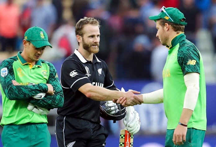 New Zealand's captain Kane Williamson, second from right, shakes and with South Africa's David Miller, right, as teammate Quinton de Kock looks down at end of the Cricket World Cup match between New Zealand and South Africa at the Edgbaston Stadium in Birmingham, Wednesday, June 19, 2019. (AP Photo/Rui Vieira)