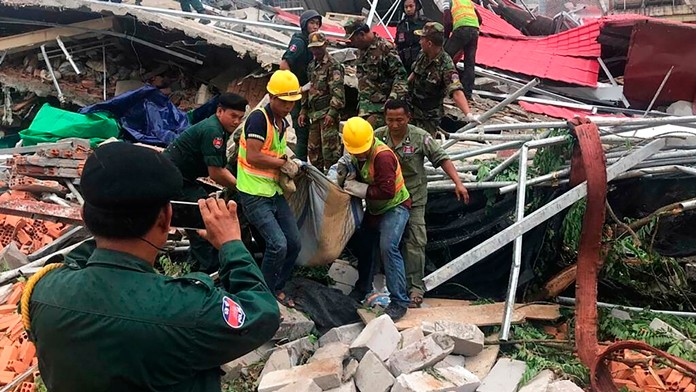 Rescue workers recover a body from the rubble of a collapsed building in the coastal city of Sihanoukville, Cambodia, Saturday, June 22, 2019. (Nokorwat News via AP)