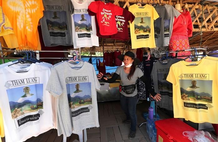 A T-shirt vendor waits for customers near the Tham Luang Nang Non cave in Mae Sai, Chiang Rai province, northern Thailand. (AP Photo/Sakchai Lalit)