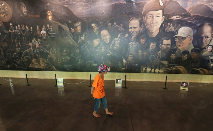 A boy watches a painting depicting the recuse mission to save 12 soccer boys and their coach near the Tham Luang cave in Mae Sai, Chiang Rai province, Thailand. (AP Photo/Sakchai Lalit)
