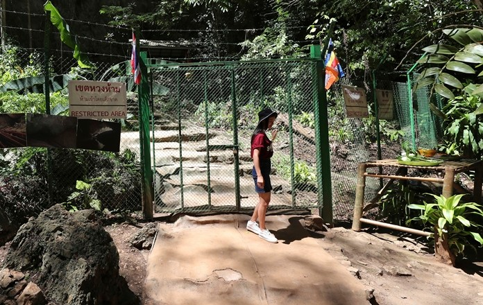 A tourist stands at the gate the Tham Luang Nang Non cave in Mae Sai, Chiang Rai province, in northern Thailand. Some of the 12 young Thai soccer players and their coach have marked the anniversary of their ordeal that saw them trapped in a flooded cave for two weeks with a commemorative marathon in northern Thailand. (AP Photo/Sakchai Lalit)