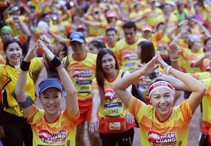 Runners warn up before the start of a marathon and biking event in Mae Sai, Chiang Rai province, Thailand, Sunday, June 23, 2019. (AP Photo/Sakchai Lalit)