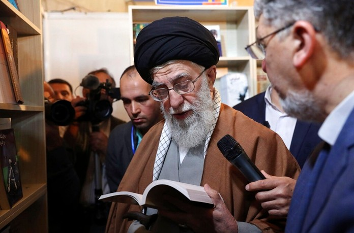 In this picture released on April 29, 2019, Iran's supreme leader Ayatollah Ali Khamenei reads part of a book while visiting Tehran's book fair in Tehran, Iran. (Office of the Iranian Supreme Leader via AP)