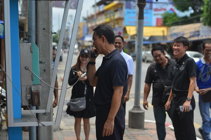 Deputy Mayor Pattana Boonsawad pretends to make a phone call from a broken phone booth, much to the delight of his staff. He said he will direct TOT to remove three abandoned pay telephone booths on South Road.