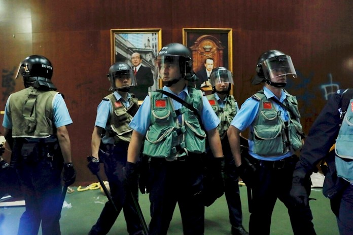 Police officers with protective gear retake the meeting hall of the Legislative Council in Hong Kong, during the early hours of Tuesday, July 2, 2019. (AP Photo/Kin Cheung)