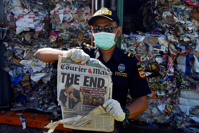 An Indonesian custom officer show off the front of a foreign newspaper among waste found in a container at the Tanjung Perak port in Surabaya, East Java, Indonesia, Tuesday, July 9, 2019. (AP Photo)