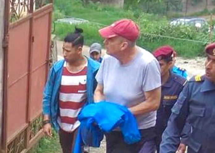 In this Monday, July 8, 2019 photo, Canadian aid worker Peter Dalglish, center wearing red cap, is brought to appear before the Kavre District Court in Nepal. (AP Photo/ Janak Raj Sapkota)