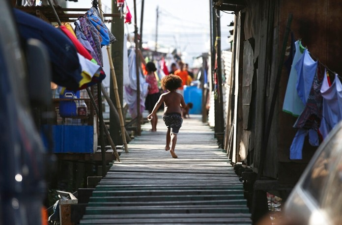 In this Nov. 15, 2018, file photo, a girl runs towards their home at Port Moresby, Papua New Guinea. (AP Photo/Aaron Favila)