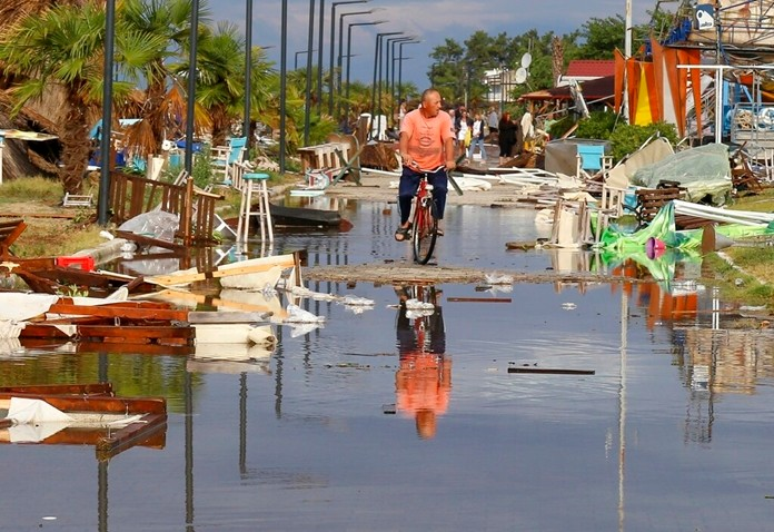 A man rides a bicycle among debris after a storm at Nea Plagia village in Halkidiki region, northern Greece, Thursday, July 11, 2019.(Giannis Moisiadis/InTime News via AP) (Giannis Moisiadis/InTime News via AP)