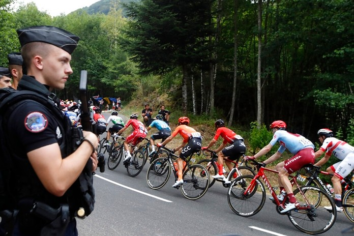 The pack rides past police officers during the sixth stage of the Tour de France cycling race over 160 kilometers with a start in Mulhouse and finish in La Planche des Belles Filles, France, Thursday, July 11, 2019. (AP Photo/Christophe Ena)