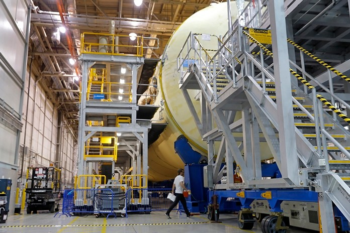 A man walks underneath the core stage for NASA's Space Launch System (SLS), which they say will carry the Orion spacecraft, and ultimately a crew, to the moon and beyond, at the NASA Michoud Assembly Facility in New Orleans, Friday, June 28, 2019. (AP Photo/Gerald Herbert)