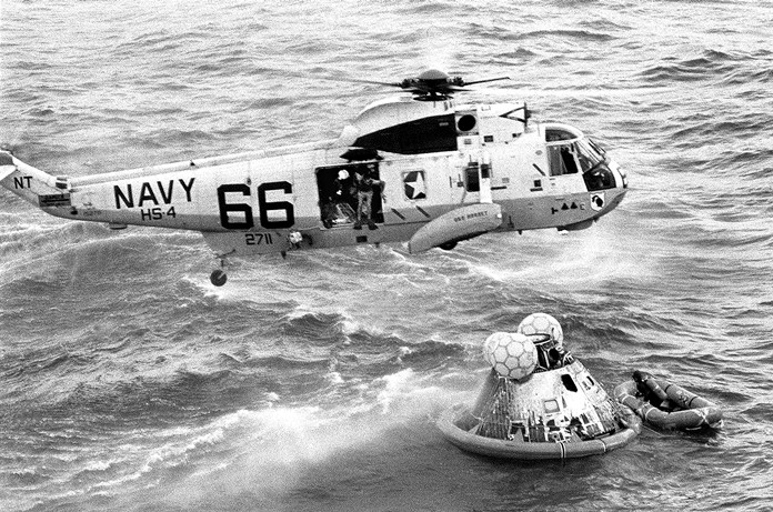 Navy UDT swimmer Clancy Hatleberg prepares to jump from a helicopter into the water next to the Apollo 11 capsule after it splashed down in the Pacific Ocean, to assist the astronauts into the raft at right July 24, 1969. (Milt Putnam/U.S. Navy via AP)