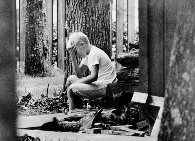 Andy Aldrin, 10, sits on a pile of cordwood in the backyard of his home in Houston while other members of his family listen to the reports of the progress of the Apollo II lunar module carrying his father, Col. Buzz Aldrin and fellow astronaut Neil Armstrong to a landing on the moon July 20, 1969. (AP Photo)