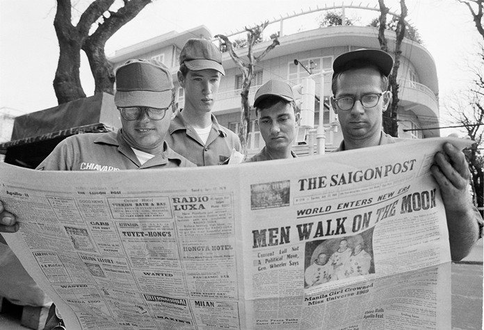 U.S. Air Force Sgt. Michael Chivaris, Clinton, Mass.; Army Spec. 4 Andrew Hutchins, Middlebury, Vt.; Air Force Sgt. John Whalin, Indianapolis, Ind.; and Army Spec. 4 Lloyd Newton, Roseburg, Ore., read a newspaper headlining the Apollo 11 moon landing, in downtown Saigon, Vietnam July 21, 1969. (AP Photo/Hugh Van Es)