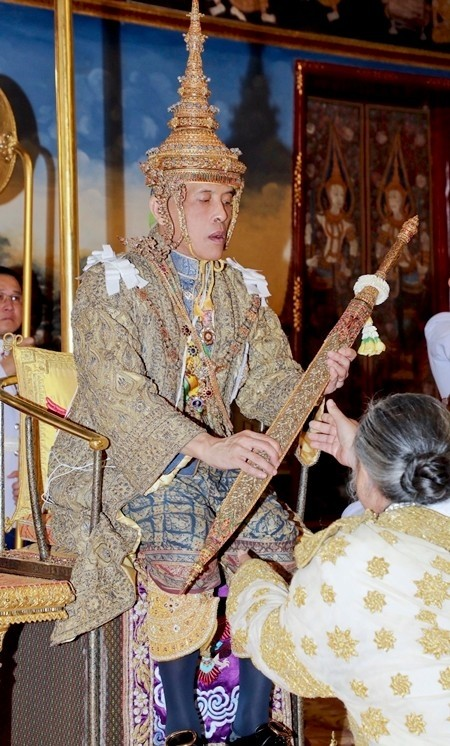 His Majesty King Maha Vajiralongkorn receives one of the many items of investiture including the royal golden plaque upon which is inscribed his royal official title, together with the royal seal of state, the royal regalia, the royal utensils, and the weapons of sovereignty.