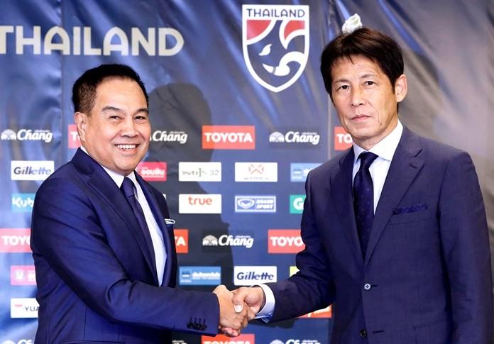 Former Japan manager Akira Nishino (right) and Thai Football Association president Somyot Pumpanmuang (left) shake hands during a press conference in Tokyo, Friday, July 19, 2019. (Masanobu Kumagai/Kyodo News via AP)