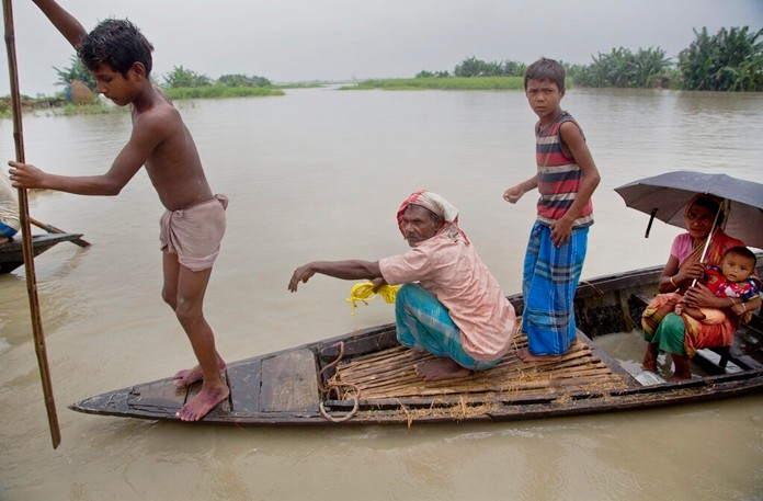 Flood affected villagers with their children travel on a boat in Katahguri village along the Brahmaputra river, east of Gauhati, India, Sunday, July 14, 2019. (AP Photo/Anupam Nath)