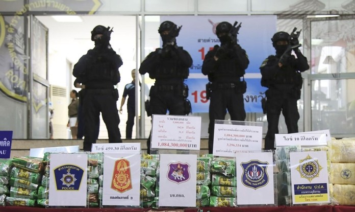 Thai policemen stand in front of packages of methamphetamines on display during a press conference at the Narcotics Suppression Bureau in Bangkok, Monday, July 15, 2019. (AP Photo)