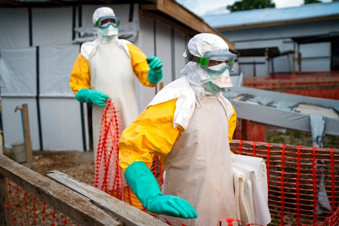 In this photograph taken Saturday July 13, 2019, health workers wearing protective suits take their shift at a treatment center in Beni, Congo DRC. (AP Photo/Jerome Delay)