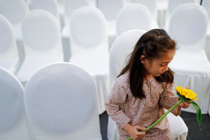 A girl holds a flower as friends and family of victims from Malaysia Airlines Flight MH17 plane crash attend a ceremony marking the fifth anniversary of the tragedy in Kuala Lumpur, Malaysia, Wednesday, July 17, 2019. (AP Photo/Vincent Thian)