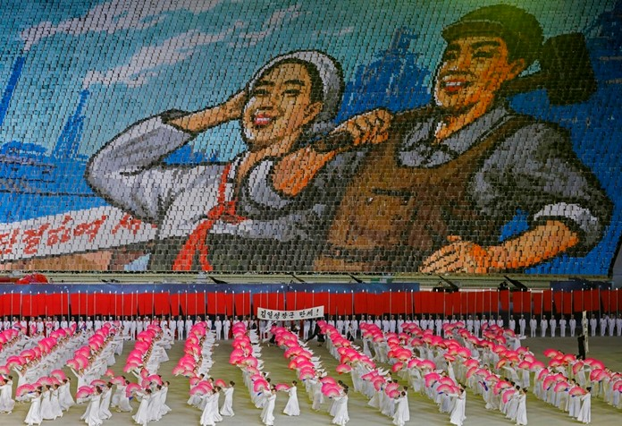 """In this Tuesday, July 16, 2019, photo, North Koreans hold cards to make an image depicting a worker and a farmer during a mass game performance of """"The Land of the People"""" at the May Day Stadium in Pyongyang, North Korea. (AP Photo/Vincent Yu)"""