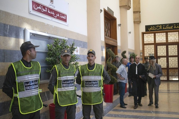 Security forces stand guard outside a court room before the start of a final trial session for suspects charged in connection with killing of two Scandinavian tourists in Morocco's Atlas Mountains, in Sale, near Rabat, Morocco, Thursday, July 18, 2019. (AP Photo/Mosa'ab Elshamy)