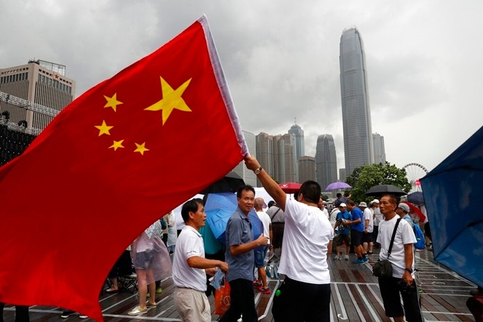 A pro-China supporter waves a Chinese national flag during a counter-rally in support of the police in Hong Kong Saturday, July 20, 2019. (AP Photo/Vincent Yu)