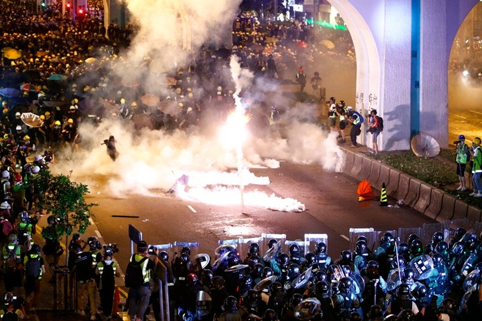 Protesters are engulfed by teargas during a confrontation with riot police in Hong Kong Sunday, July 21, 2019. (Lo Kwanho/HK01 via AP)