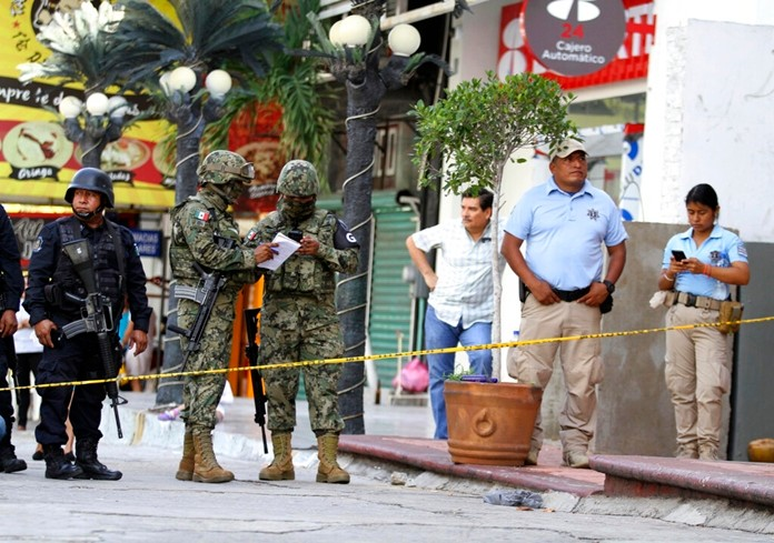 Soldiers and State Police officers guard an area where gunmen killed and wounded multiple people inside a bar in Acapulco, Mexico, Sunday July 21, 2019. (AP Photo/Bernardino Hernandez)