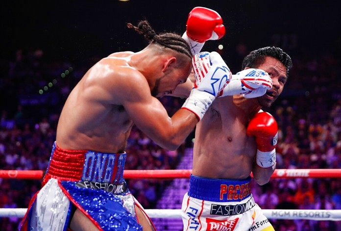 Manny Pacquiao, right, and Keith Thurman exchange punches during their welterweight title fight Saturday, July 20, 2019, in Las Vegas. (AP Photo/John Locher)